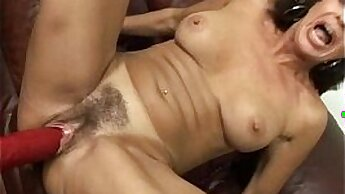 Aroused brunette MILF fucks herself with large dildo on the laundry